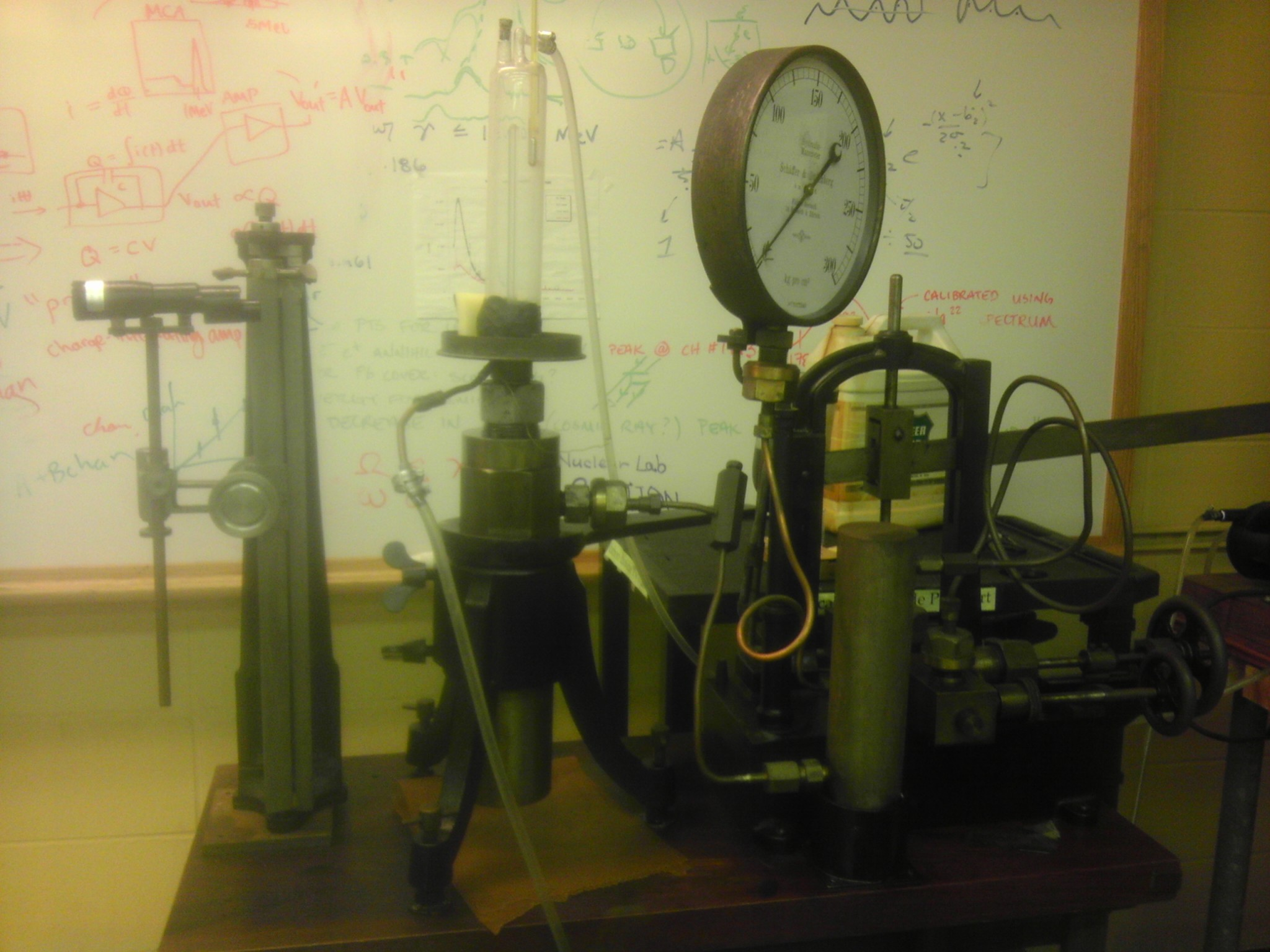 The apparatus. We measured the height of the mercury with the telescope on the left. The pressure gauge is to the right and the CO_2 sample is in the glass tube.